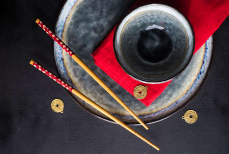 Rustic table setting with chopsticks for dinner in asian style  on dark wooden table with copyspace