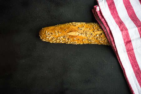 Healthy homemade bread with seeds on dark wooden background with copyspace