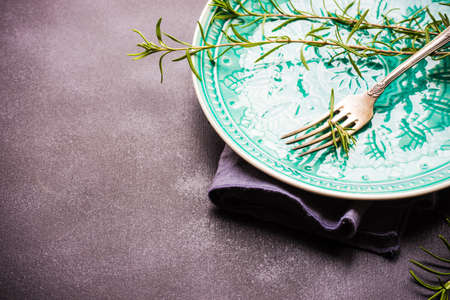 Summer time table setting with fresh rosemary spice on rustic background with copy space