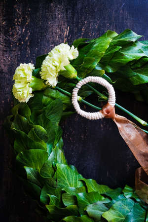 circlet of carnation flowers on dark wooden background with copyspace
