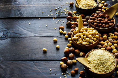 Different types of hazelnuts on dark wooden background with copyspace Imagens