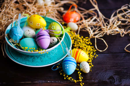 Easter holiday card with colored easter eggs and rustic tableware on dark wooden table with copy space