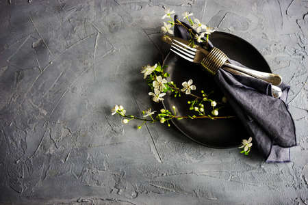 Spring floral concept with blooming cherry tree branches and serving with rustic tablewares on dark wooden table 写真素材