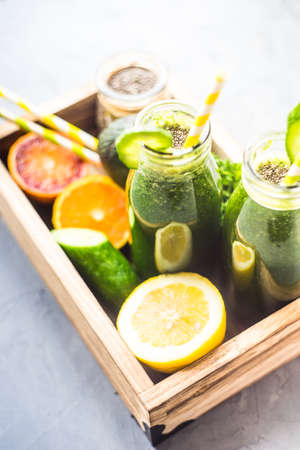 Organic and healthy green smoothie with banana, spinach, avocado, citrus fruits and chia seeds in a glass bottles on a rustic background withcopy space