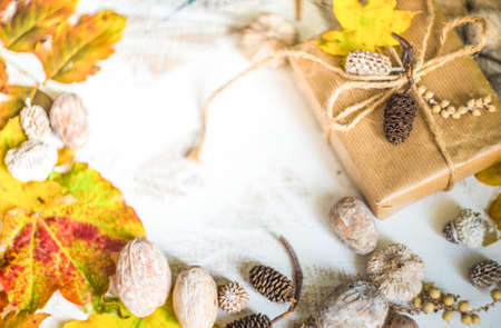 Autumnal concept with bright yellow leaves and gift box in rustic style with copyspace Stock Photo