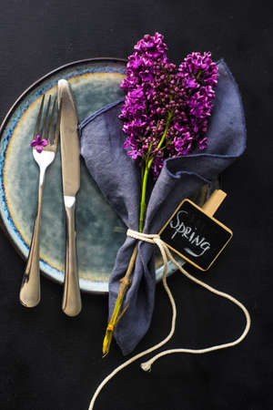 Spring table setting  with lilac flowers on rustic table with copy space