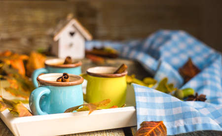 Autumnal concept with mup of coffee with spices, cinnamon stick and anise star on rustic wooden  background full of bright oak yellow leaves and acorns