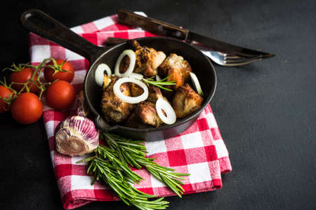 Grilled meat on vintage pan with fresh onion, rosemary and tomato  as a healthy food concept