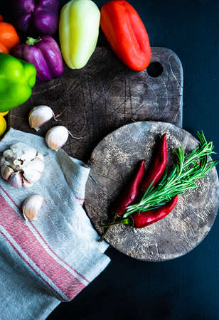 Organic food concept with fresh different colors bell peppers on rustic background with copy space