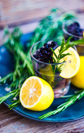 Traditional italian lemon alcohol drink limoncello with pieces of lemon and rosemary herb on dark wooden table Stock Photo - 108037624