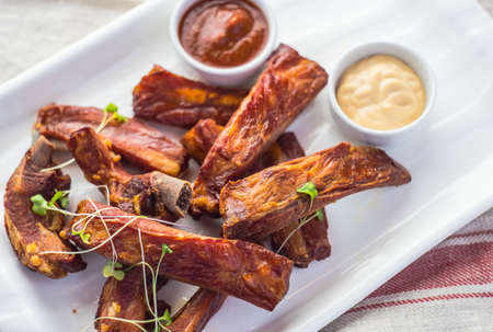 juicy barbeque pork ribs with ketchup sauce on wooden table Archivio Fotografico
