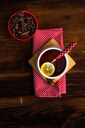 Cup of tea with lemon on red textile napkin