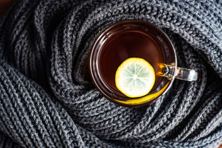 Cup of tea with lemon and warm knitted scarf as a winter concept