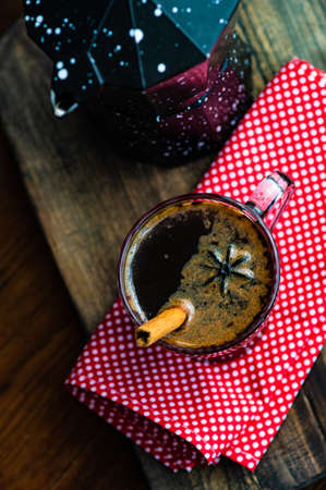 Cup of coffee with spices like cinnamon stick and anise star on wooden background