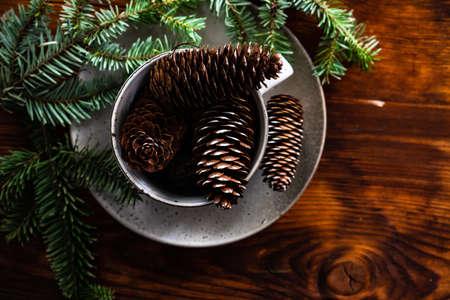 Festive table setting with ceramic plate and cup full of pine cones and decor on wooden background