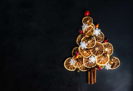 Christmas holiday concept with oranges and cinnamon  shaped in Christmas tree on dark wooden background