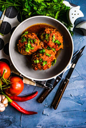 Meatballs in spicy tomato sauce with coriander and garlic on rustic table Stock Photo