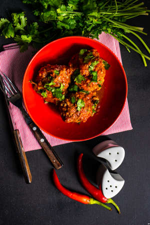 Meatballs in spicy tomato sauce with coriander and garlic on rustic table Stock fotó