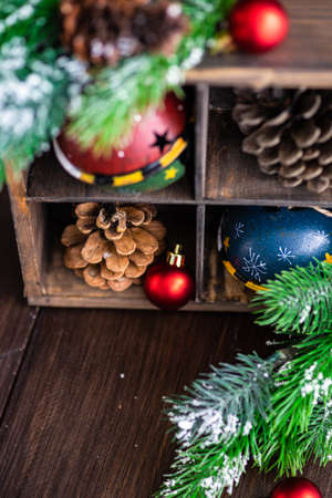 Christmas concept with vintage wooden box full of jingle bells and cones on rustic background