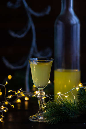 Christmas lights and glass with limoncello drink on dark wooden background Stock Photo