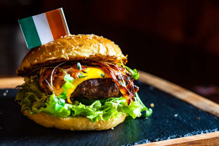 Close up of Irish hamburger with meat, vegetables and bacon on rustic background with copy space