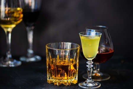 Set of glasses with alcohol drinks on dark background with copy space