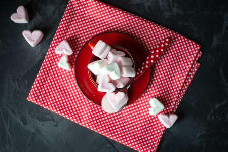 St, Valentines concept with red vintage cup full of heart shaped marshmallow on rustic background Banque d'images - 115465693