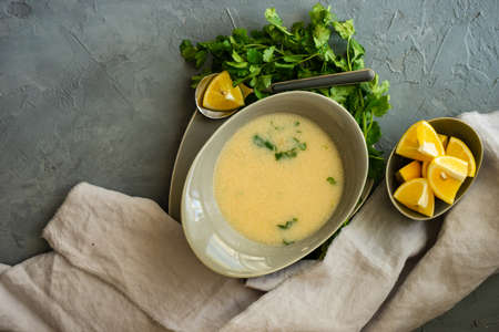 Traditional georgian chicken soup Chikhirtma with coriander and lemon on rustic background with copy space Фото со стока