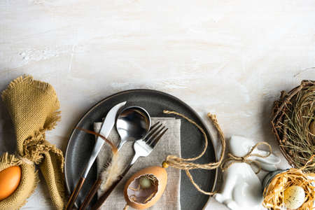 Festive table setting for easter dinner on white wooden table with copy space