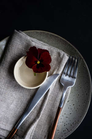 Spring table setting with red tricolor viola flower on dark wooden background with copy space