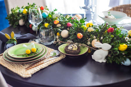 Festive table setting for Easter holiday dinner decorated with flowers and eggs