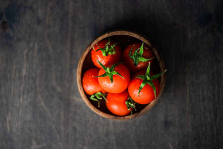 organic fresh cherry tomatoes in a bowl on rustic background with copy space 写真素材