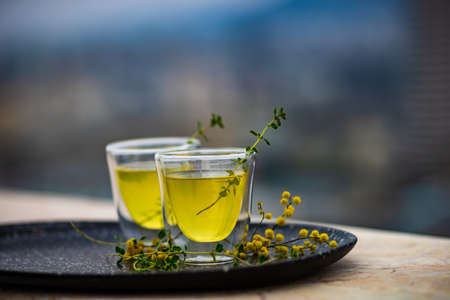 Traditional italian lemon alcohol drink limoncello with pieces of lemon and rosemary herb on dark wooden table Stock Photo - 118828530