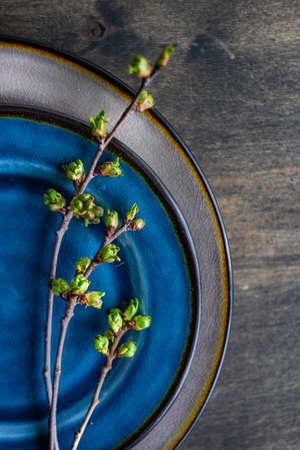 Spring table setting in rustic style decorated with cherry bloom tree branches
