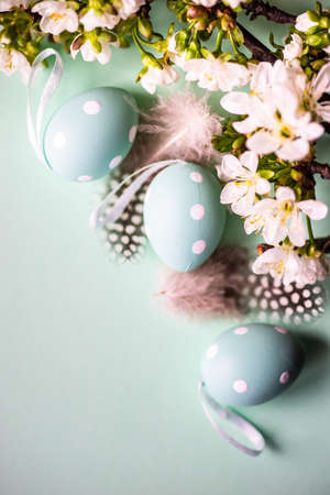 Easter holiday card concept with green  colored eggs and cherry blossom flowers  on pastel green background