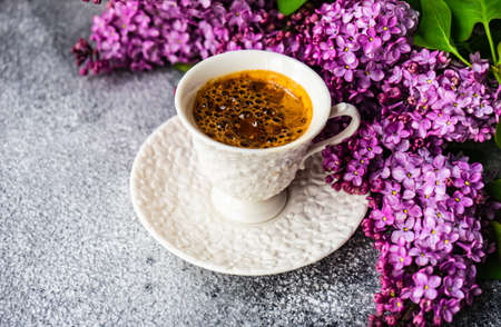 Spring floral frame concept with lilac flowers and cup of coffee on grey background with copy space Stock fotó