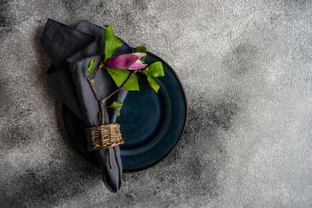Spring table setting with magnolia blossom on grey concrete background with copy space