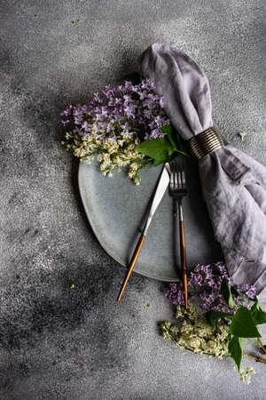 Frühlingstischdekoration mit schönen lila Blumen auf grauem Betonhintergrund mit Kopienraum Standard-Bild