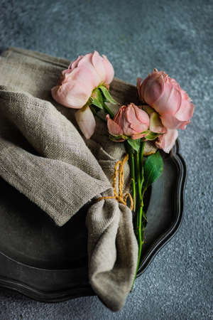 Festive table setting with beautiful roses, modern plates and cutlery on rustic grey background with copy space