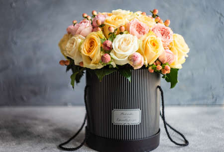 Floral weddinf gift concept with box full of roses on grey background