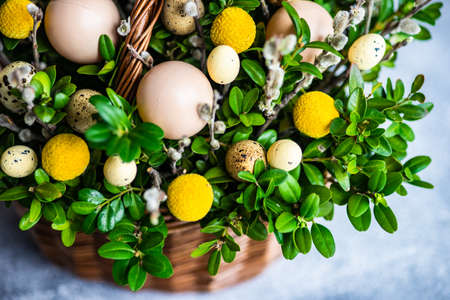 Easter card concept with floral composition with boxwood and colored eggs Reklamní fotografie