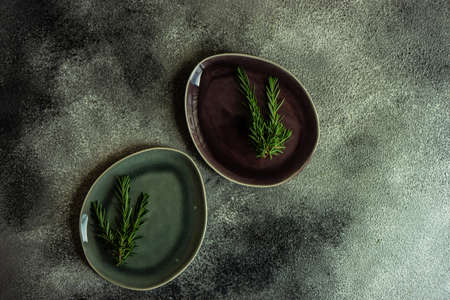 Table setting with fresh rosemary on dark stone table with copy space
