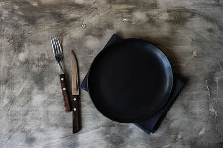 Empty black plate and rustic cutlery set on grey table with copy space 版權商用圖片