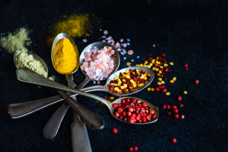 Variety of spices on dark concrete background with copy space