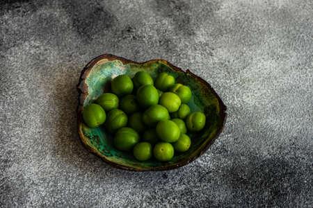 Green cherry plum in ceramic bowl on grey concrete table