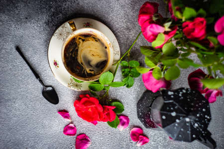 Coffee set with red roses and coffee pot on concrete background with copy space