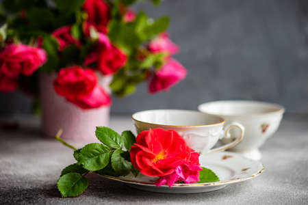 Tea set with red roses on concrete background with copy space