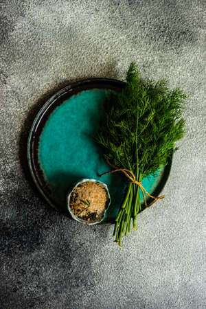 Cooking concept with ceramic plate  with spicy salt  and fresh dill herb