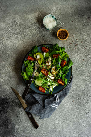 Eat green concept with organic fresh vegetable salad in ceramic bowl on concrete background with copy space