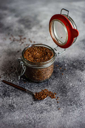 Organic food concept with flax seeds on grey concrete  background